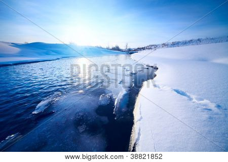 Winter river with ice on a coast at clear sunny weather
