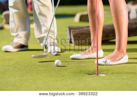 Pessoas, homem e mulher, só de pés, jogando golfe em miniatura em um dia lindo de Verão