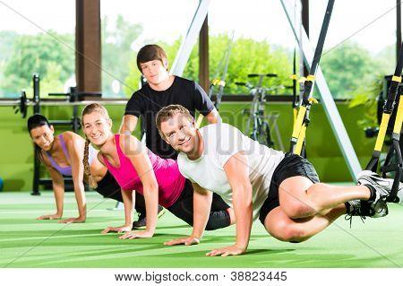 Grupo de personas ejercer con entrenador de suspensión en el gimnasio o gimnasio