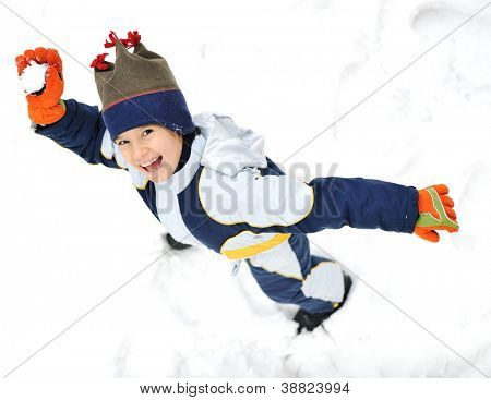 Happy child throwing snowball