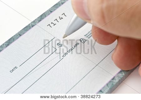 A person holding a pen signing cheque