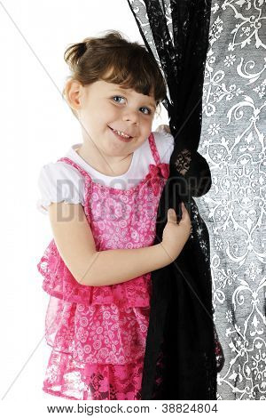 An adorable little girl shyly emerging from behind a black curtain the she's twisted around her hand.  On a white background.