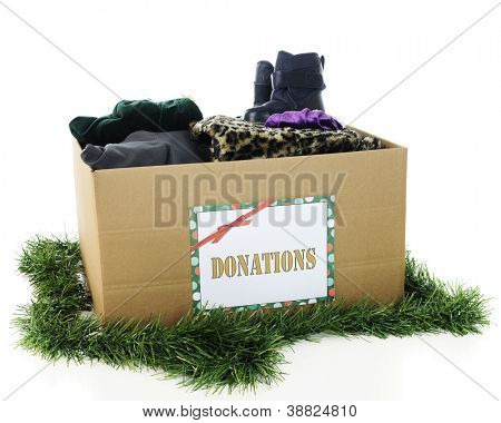 """A large corrugated box with a holiday """"Donation"""" sign.  The box is filled with assorted winter clothing and surrounded by Christmas garland.  On a white background."""