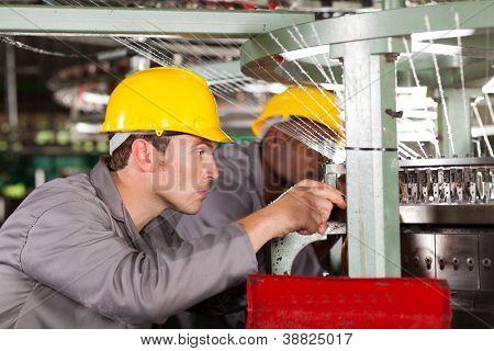 two textile weaving machine mechanics repairing loom