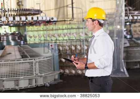 textile production manager working inside factory