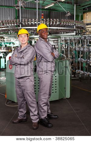 two industrial workers full length portrait in factory