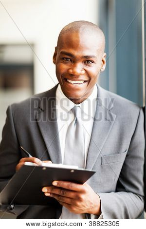 smiling african american office worker writing report in office