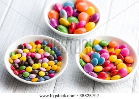 Three different sizes of colorful candies in ceramic bowls