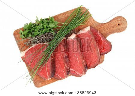fresh ripe marble beef meat on wooden plate with thyme and chives isolated on white background