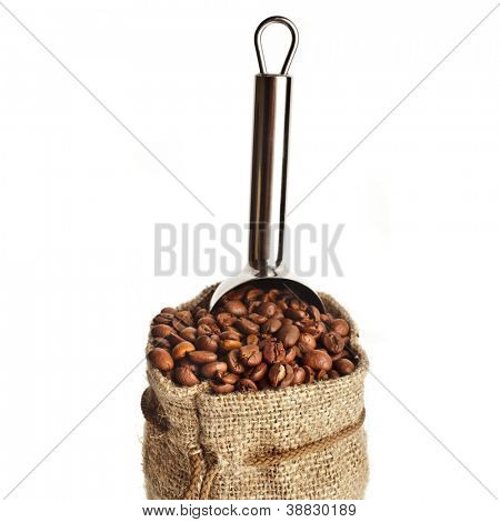 Burlap sack of coffee beans with metallic scoop on white background