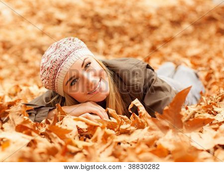 Image of pretty woman laying down on the ground covered dry autumnal foliage in beautiful park