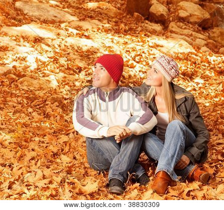 Picture of two lovers sitting down on ground covered autumnal dry foliage and looking up in sky