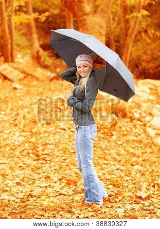 Photo of lovely woman walk under umbrella in rainy day in autumnal park
