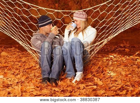 Image of beautiful young couple sitting in hammock and drink hot chocolate