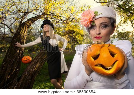 Halloween concept: sexy ladies vampire with halloween pumpkins in forest