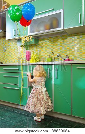 Little girl on kitchen with a bunch of  balloons.