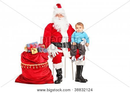 A Santa Claus and small child on his lap posing next to a bag full of gifts isolated on white background