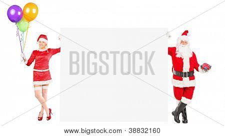 Full length portrait of a male and female Santa Clauses holding a blank panel isolated on white background