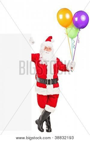 Full length portrait of a happy Santa claus standing next to a blank billboard and holding balloons isolated on white