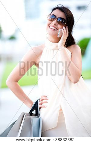Beautiful woman shopping and talking on her mobile phone