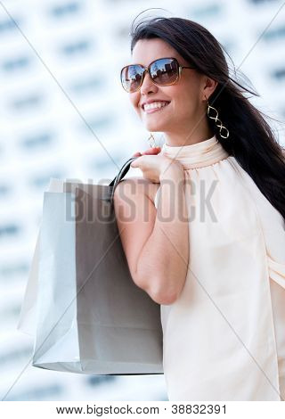 Beautiful summery shopping woman holding bags and smiling
