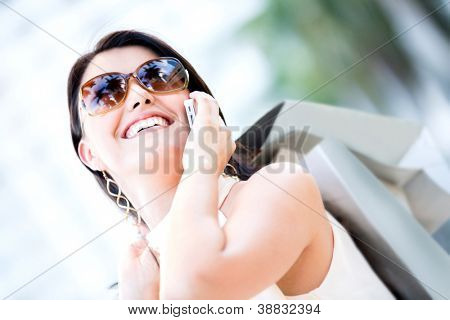 Female shopper on the phone and holding shopping bags