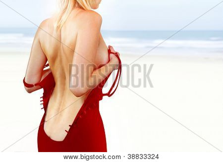 woman in red dress with tattoo on her back sitting near sea shore