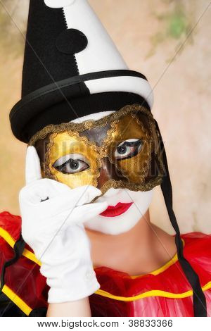 Painted pierrot holding a leather venice mask