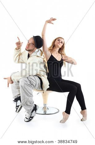 Rapper and ballerina sit on yellow chair and pose isolated on white background.