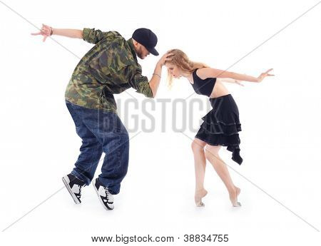 Gymnast in black dress and rapper stand on tiptoe, arms tossed back isolated on white background. Man keeps head of woman.