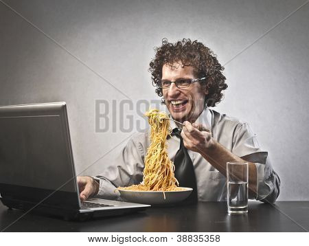 Man is eating red spaghetti while he is using a laptop computer