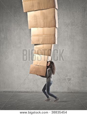Brown girl holding several boxes in equilibrium