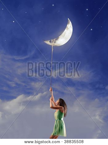 Beautiful brown girl holding the moon with a rope