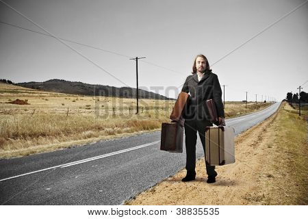 Blonde man, on a long road of countryside, holding many suitcases