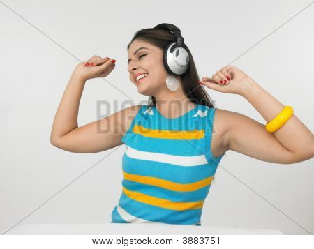 Young Asian Female Of Indian Origin Enjoying Music