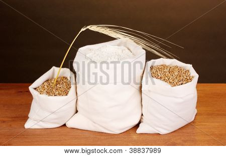 Flour and wheat grain on wooden table on dark background