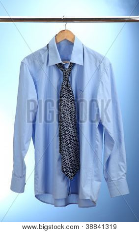 shirt with tie on wooden hanger on blue background