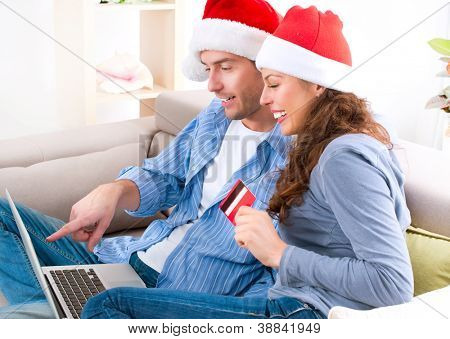 Christmas Shopping On-line . Happy Smiling Couple Using Credit Card to Internet Shop. Young couple with laptop and credit card buying online. Christmas and New Year Gifts. e-shopping