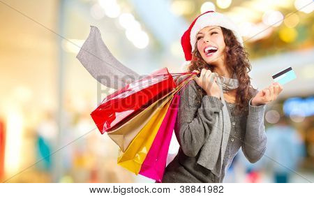 Compras de Natal. Bela garota feliz com cartão de crédito em Shopping Center. Sacos de compras. Compras