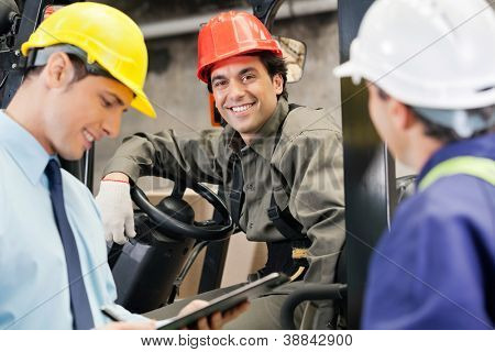 Portrait of happy young forklift driver with supervisor holding clipboard at warehouse