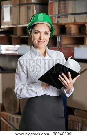 Portrait of confident young female supervisor with book standing at warehouse