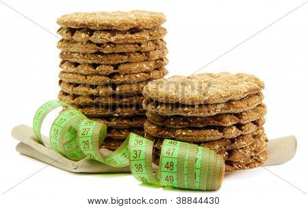 tasty crispbread and measuring tape, isolated on white