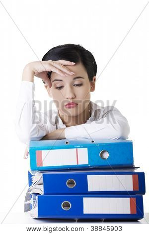 Sad woman with ring binders sitting at the desk. Tired and exhausted business woman.
