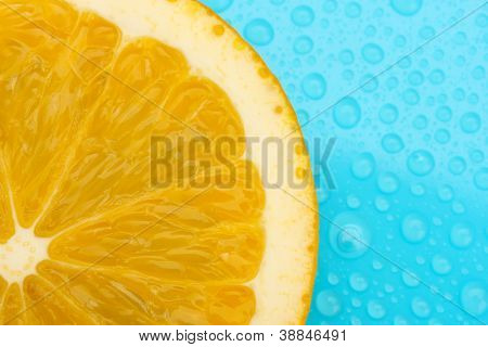 Slice of lime with drop on blue background