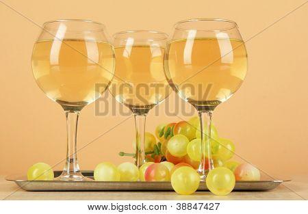 White wine in glass on salver on beige background