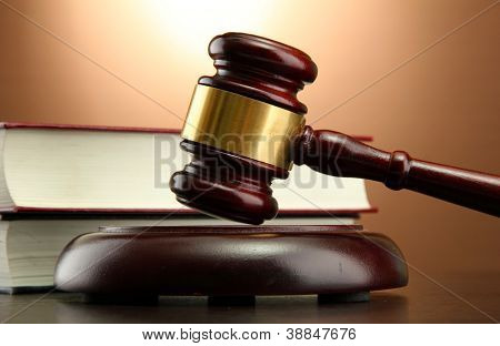 wooden gavel and books on wooden table, on brown background