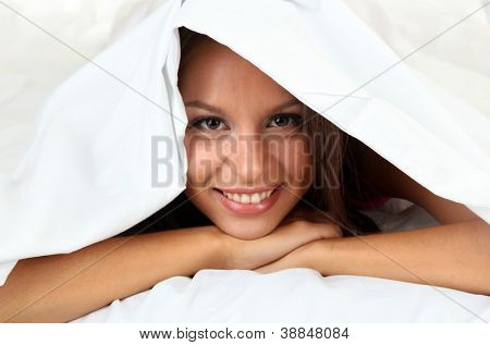 young beautiful woman looking out from coverlet