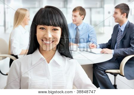 Successful asian business woman with her staff in background at office