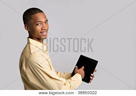 Close up of Black Businessman Hand Pointing to Tablet PC on Grey Background
