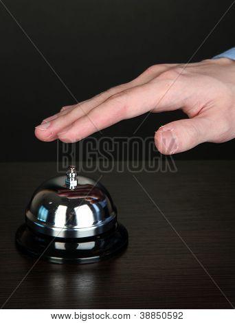 Hand Klingeln im Service Portier auf Holztisch auf schwarzem Hintergrund